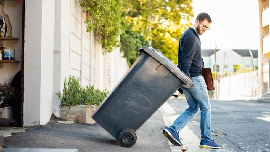 A man pulling out a wheeled dumpster