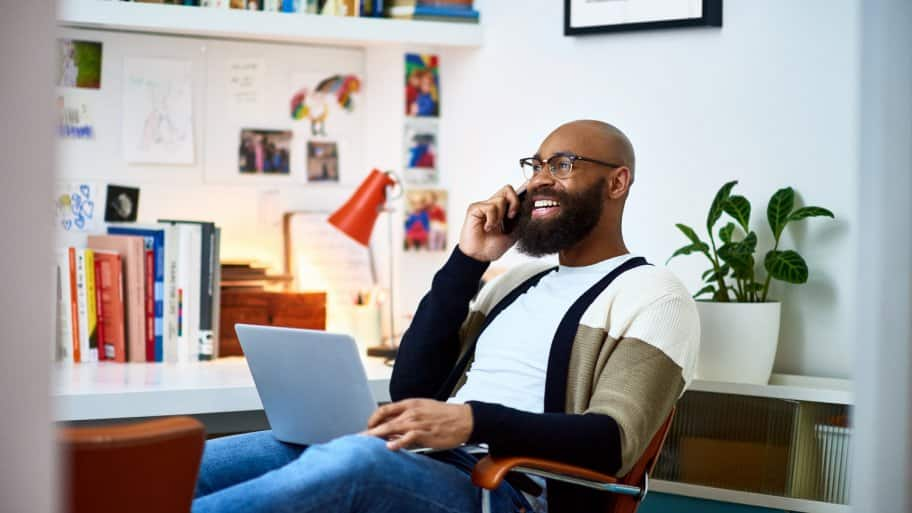 A man talking on his phone while using his laptop