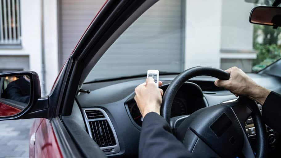 A man using a remote control to open her garage door