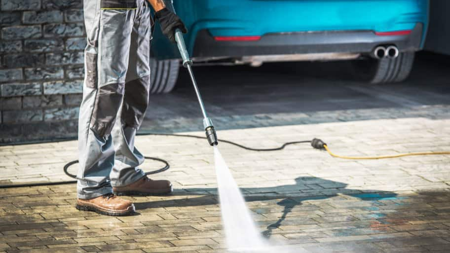 A man cleans his home's driveway using a pressure washer
