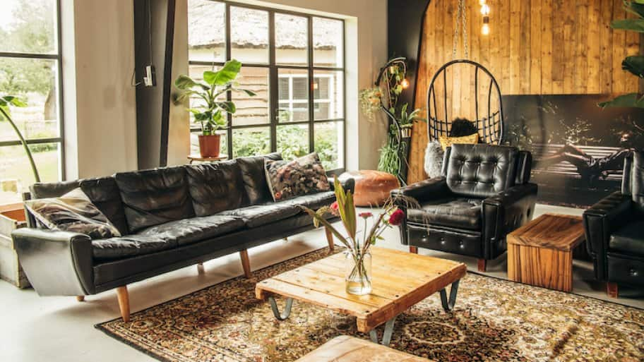 a midcentury modern style sofa in a loft style livingroom with wood accents, a wood wall, and hanging lighting (Photo by Hugo - stock.adobe.com)