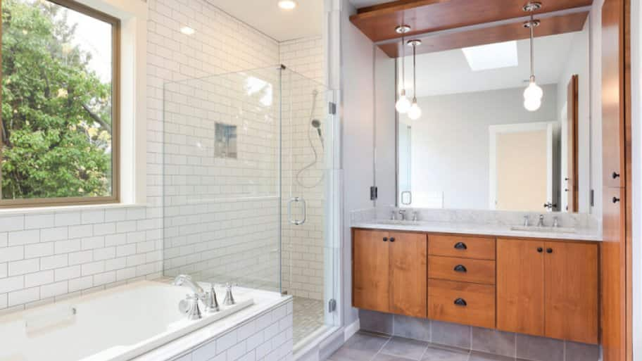 Modern bathroom with white subway tile and wood cabinets (Photo by chuckcollier/E+/Getty Images)