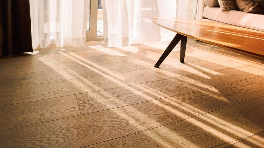 A sunlit modern living room with laminate flooring