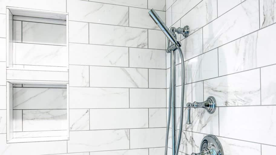 A modern shower with white tiles