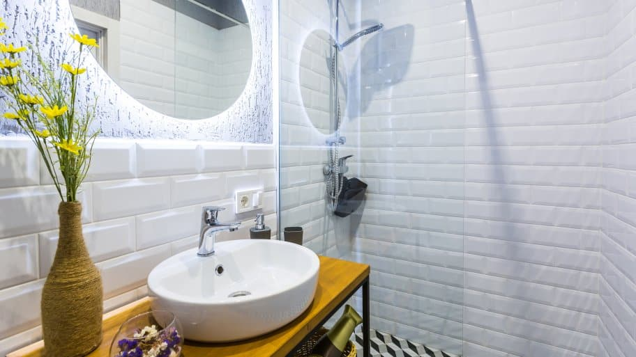 Modern small bathroom with white tile walls, glass rain shower, backlit round mirror, and vessel sink on narrow wood table