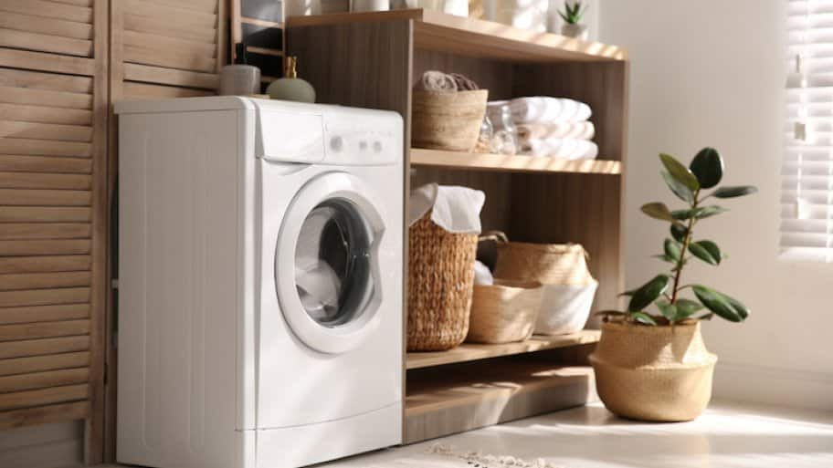Modern washing machine and shelving unit in laundry room interior