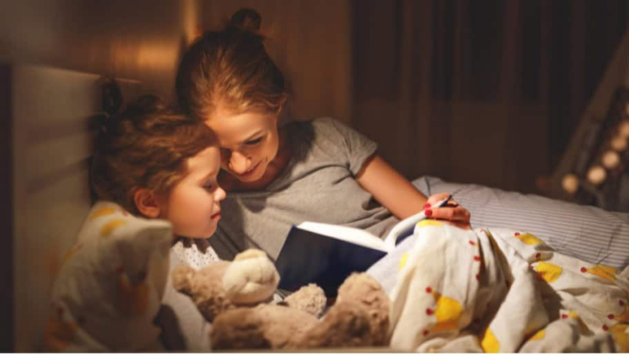 Mother and child reading at night under light (Photo by Evgeny Atamanenko / Shutterstock.com)