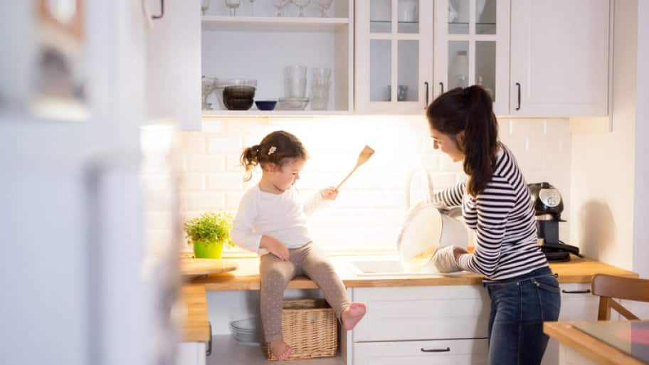Mother and daughter laughing at kitchen sink