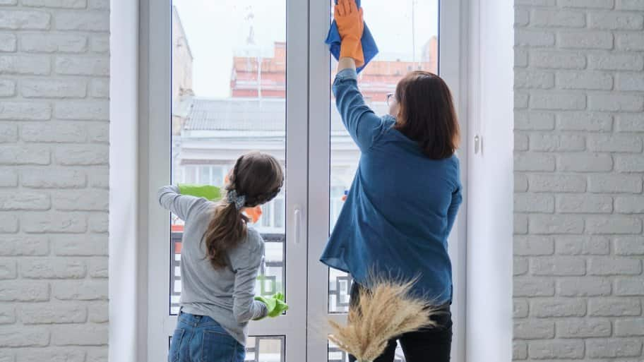a mother and daughter cleaning tall windows in home (Photo by Valerii Honcharuk - stock.adobe.com)