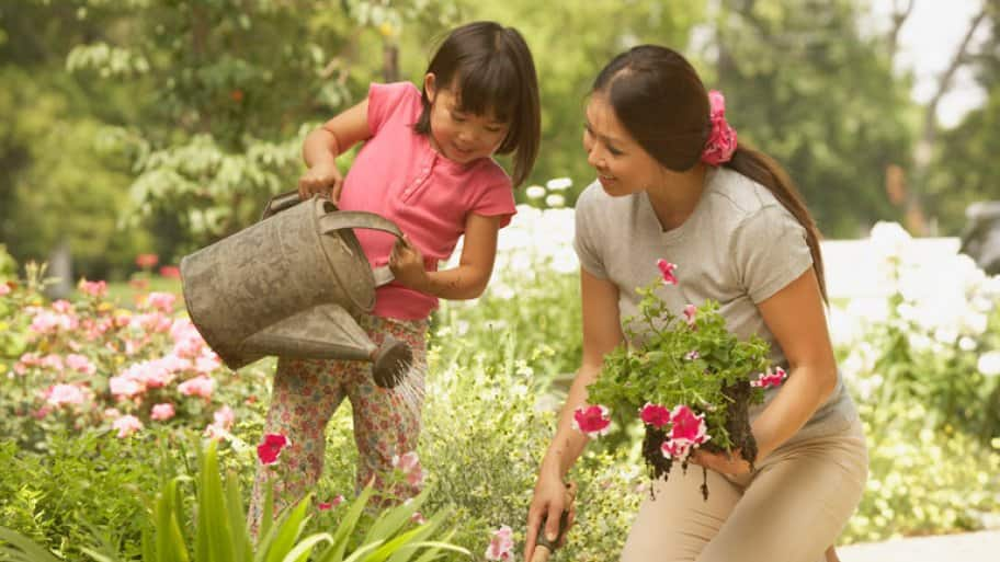 A mother and her daughter planting and watering their garden