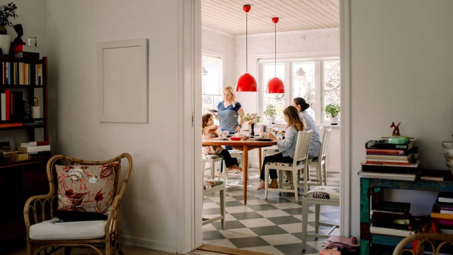A mother having breakfast with her daughters in bright kitchen