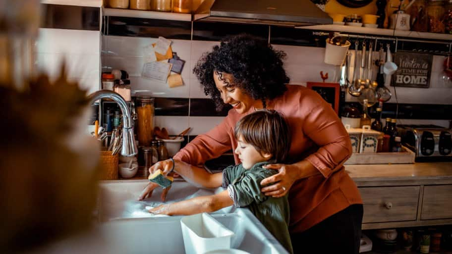 A mother with her son doing the dishes