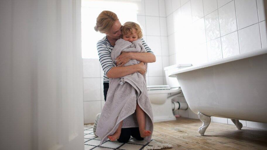 A mother in a bathroom wrapping her daughter with a towel