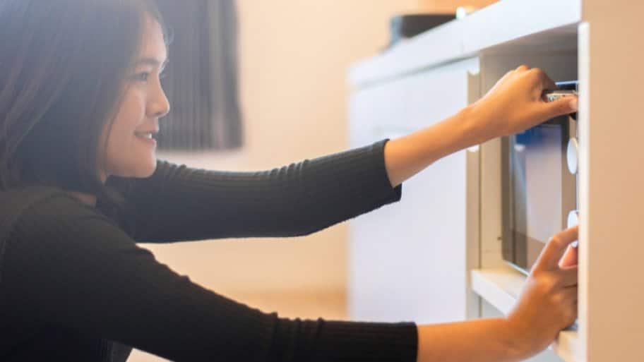 Woman programming microwave
