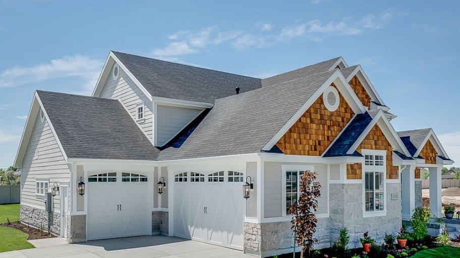 Garage view of home with shingle roof