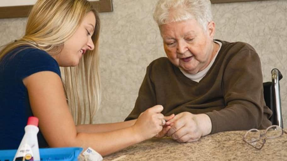 A young women gives a manicure to an elderly woman.