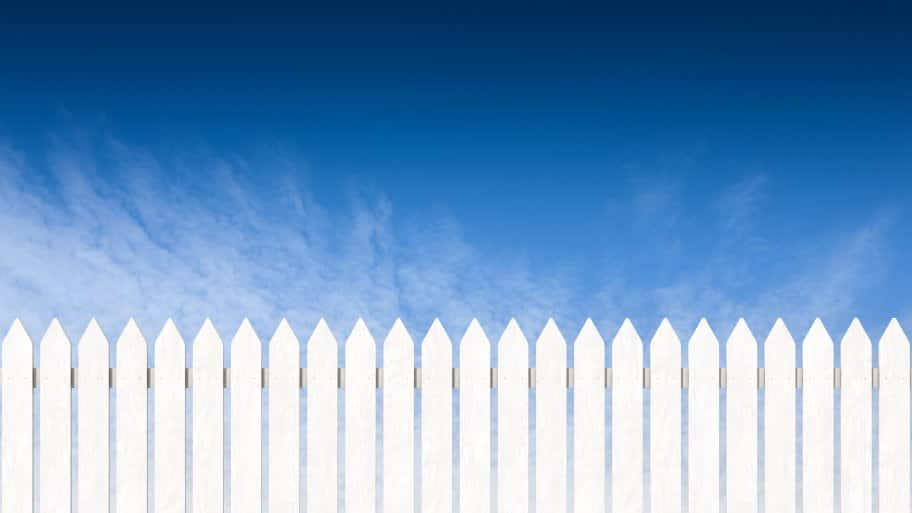 a vertical wood picket fence