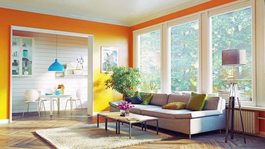 Brightly orange painted livingroom with white trim