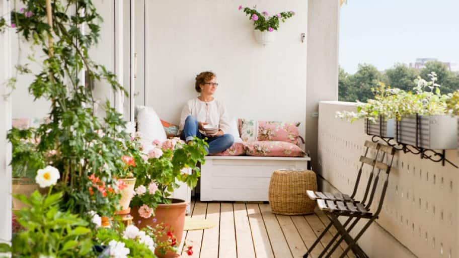 Woman relaxing on balcony with plants (Photo by  Johner Images via Getty Images )