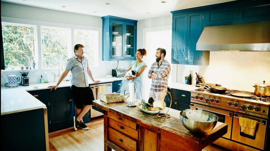 Friends talk in kitchen with painted cabinets