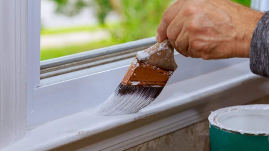 Man's hand painting window trim white