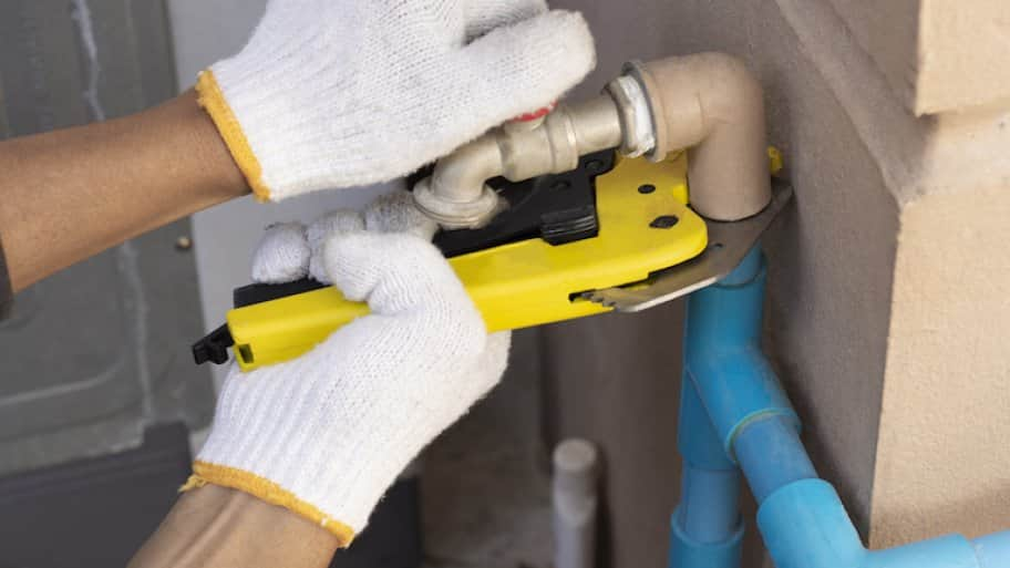 gloved hands holding pipe cutter against pipe