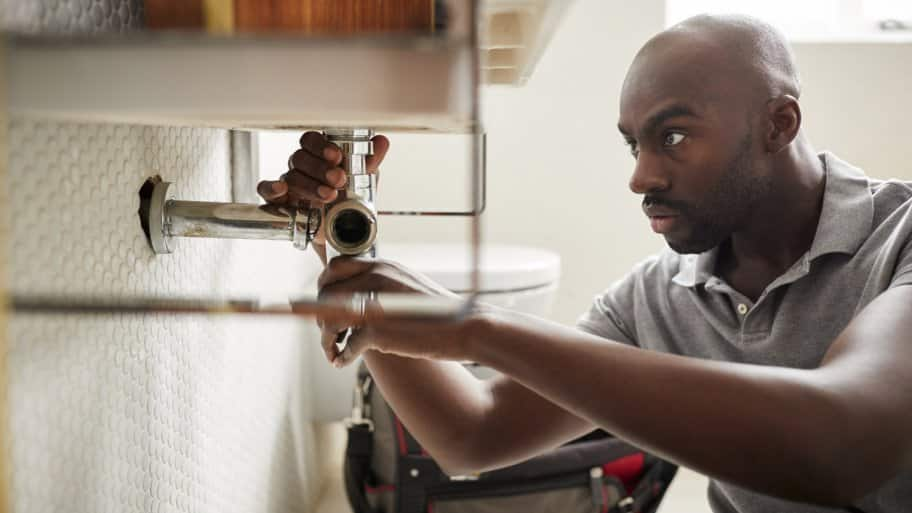 Plumber fixing a bathroom sink (Photo by Monkey Business - stock.adobe.com)