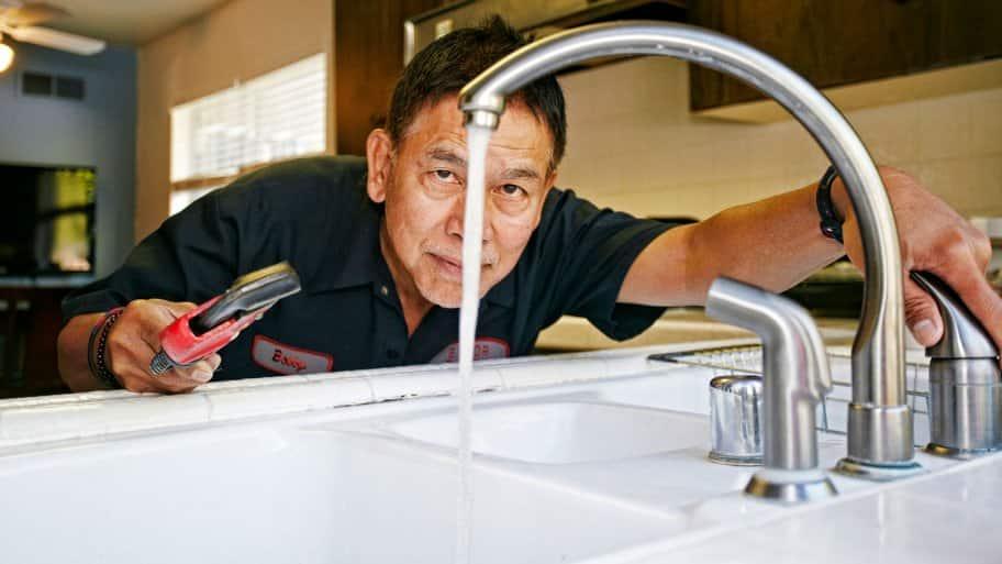 Plumber inspecting water flow