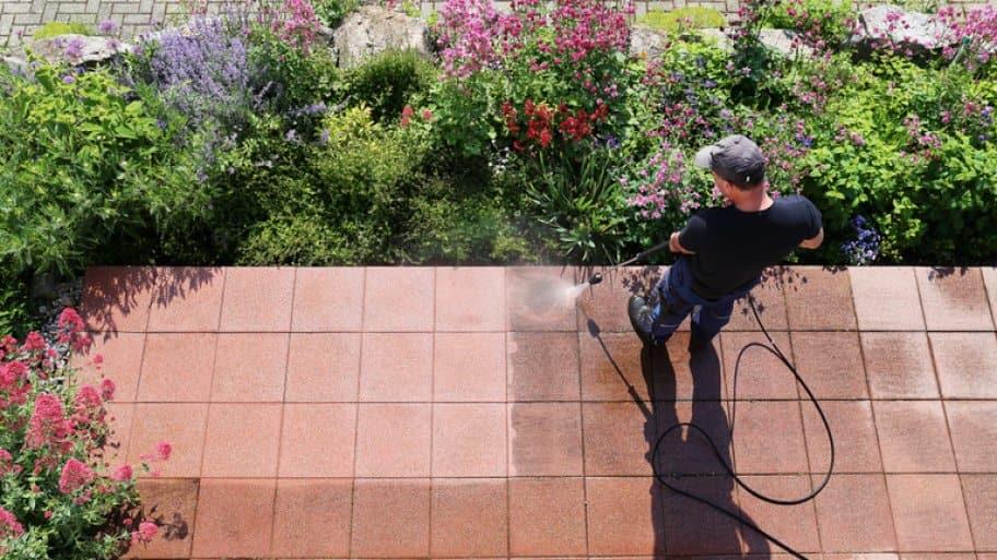 Pro power washing an outside stone patio (Photo by Marina Lohrbach / Shutterstock.com)