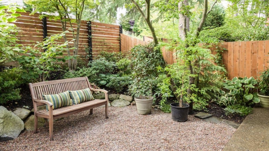 a light wood privacy fence surrounds a private yard with plants, bushes, a bench, and gravel