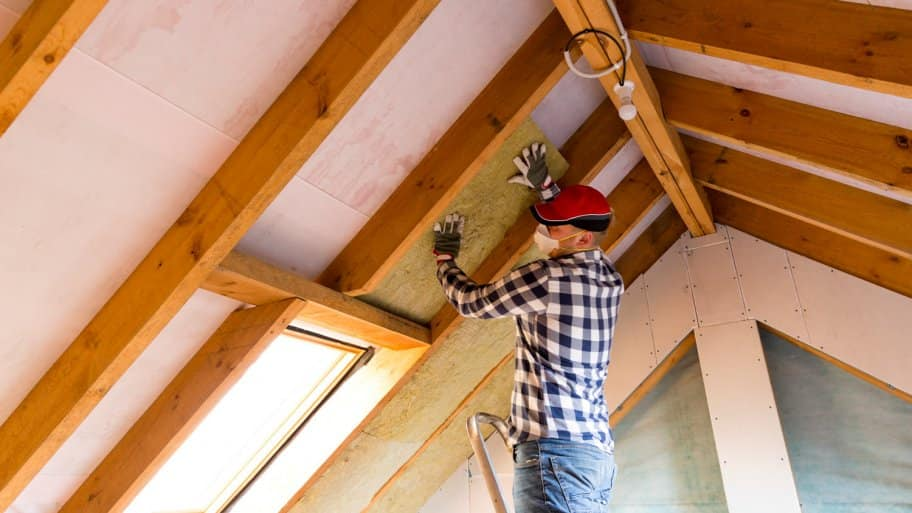 A professional insulating an attic at a house