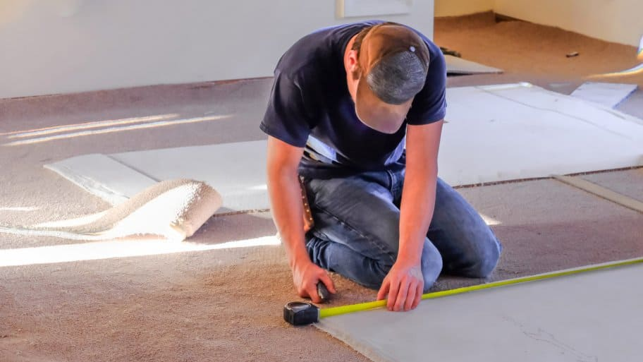 A professional measuring prior to installing a carpet