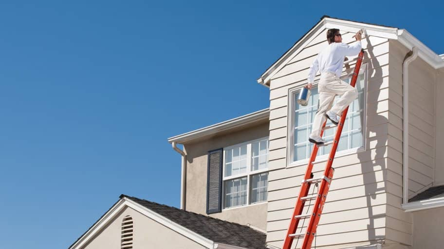 A professional standing on a ladder paints the exterior of a house