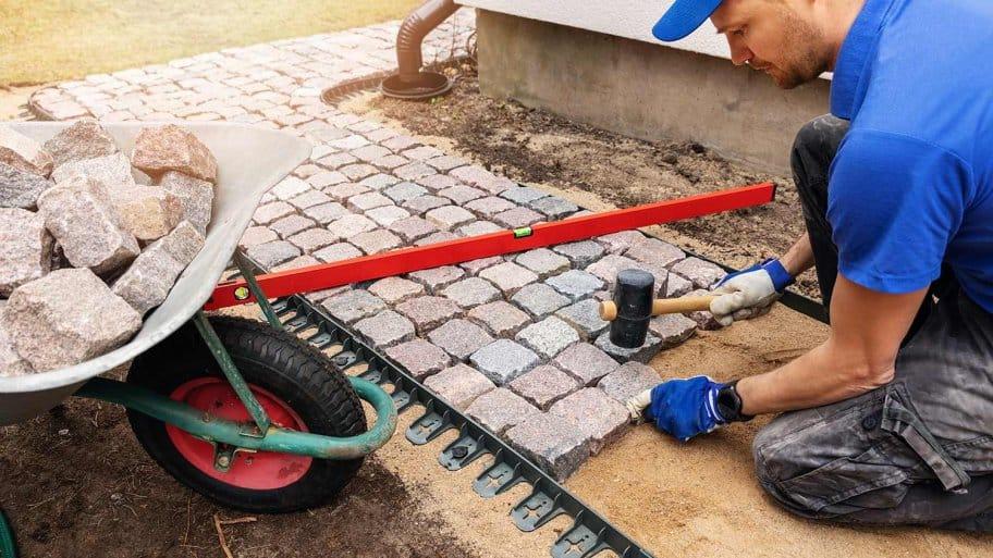 Professional paver laying sidewalk