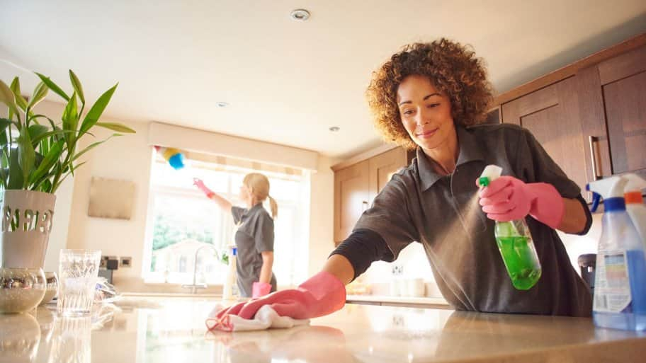 Two professionals cleaning a house's kitchen