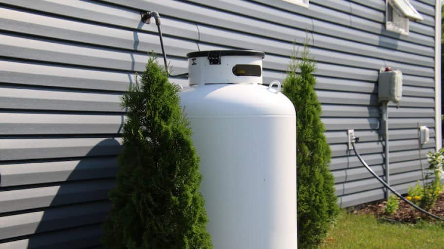 propane tank between two bushes along side of house (Photo by © David - stock.adobe.com)