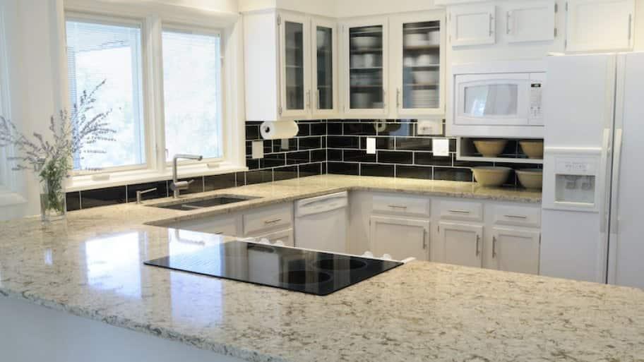 modern kitchen with white cabinets, black backsplash, and quartz countertop