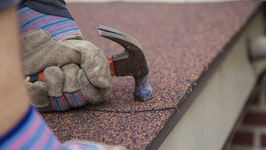 roofer hand nailing asphalt shingles