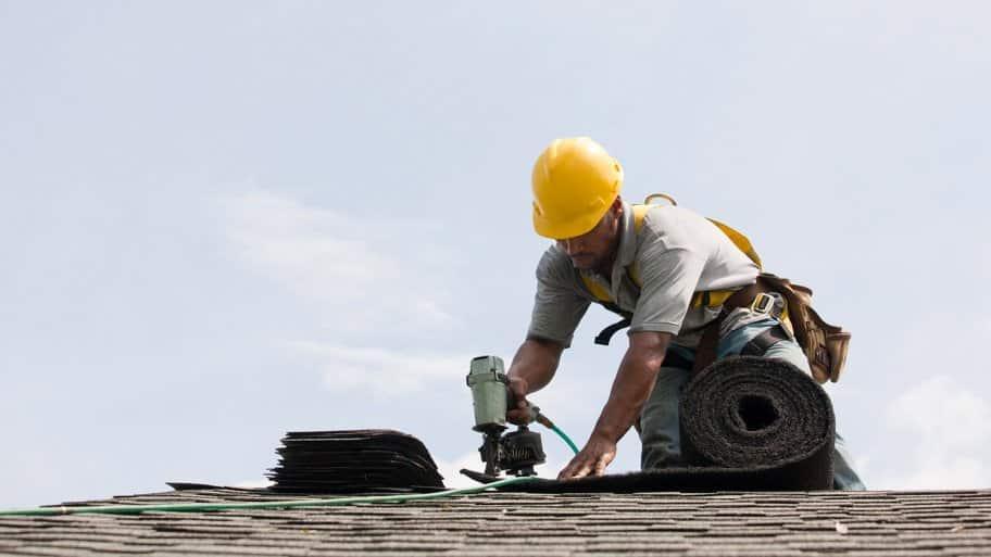 Man installs shingles to roof