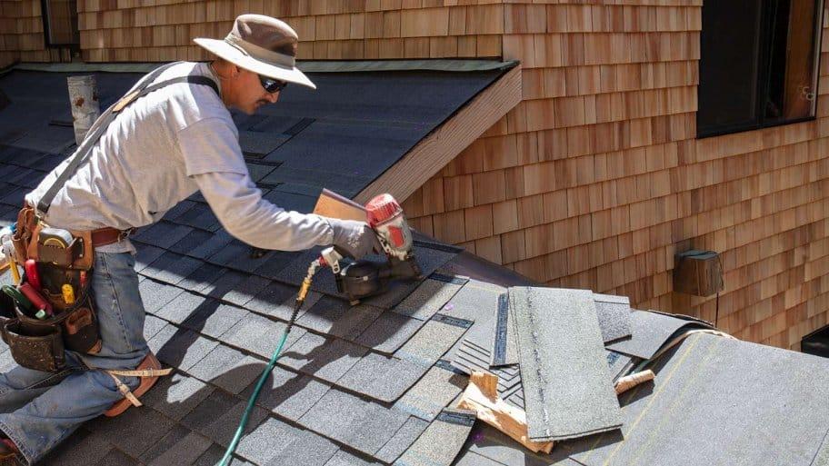 Roofer installs asphalt shingles (Photo by Bill Oxford / E+ via Getty Images)