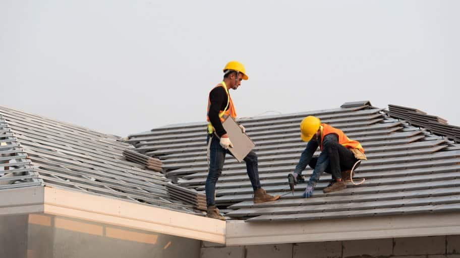A group of roofers installing ceramic tiles on a roof