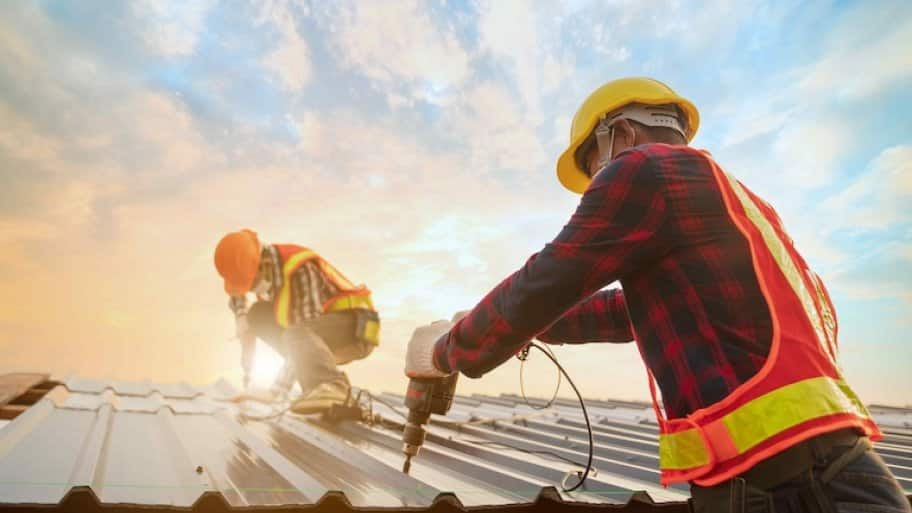 Two roofing workers in protective uniforms and wearing gloves, using electric tools and installing ironing metal sheets on top of a new roof (Photo by Attasit - stock.adobe.com)