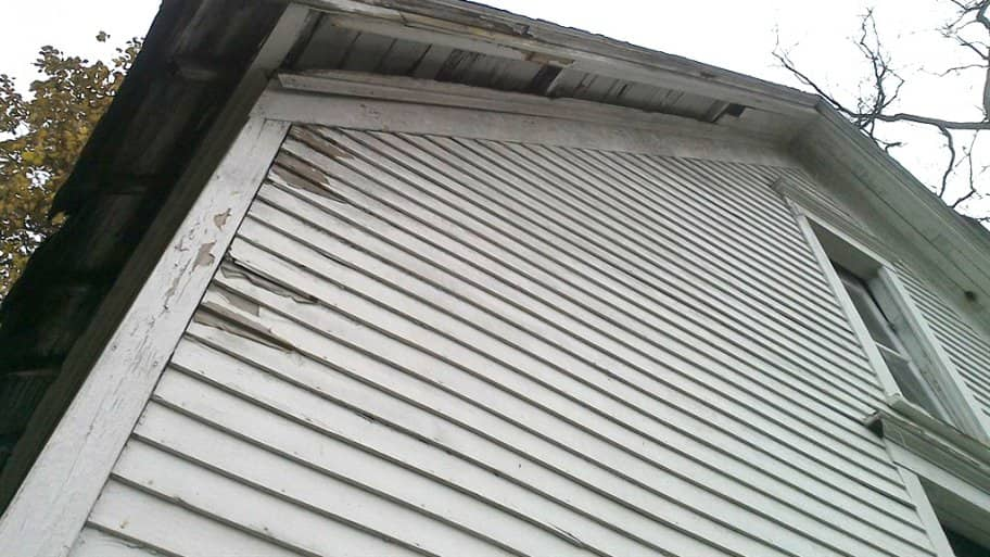 Rotten soffit and old roofing on shed