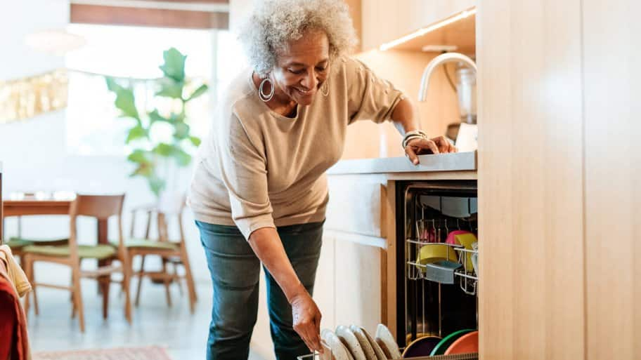 A senior woman loading the dishwasher with dishes