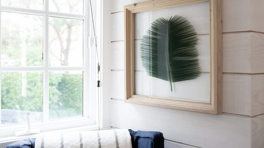 Shiplap accent wall with framed palm leaf next to open window and navy chair