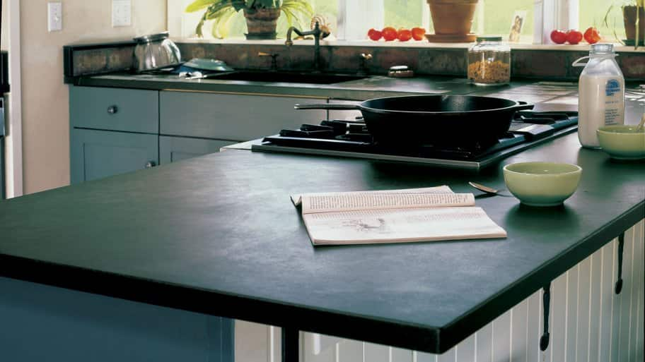 A soapstone countertop with a frypan on the stove