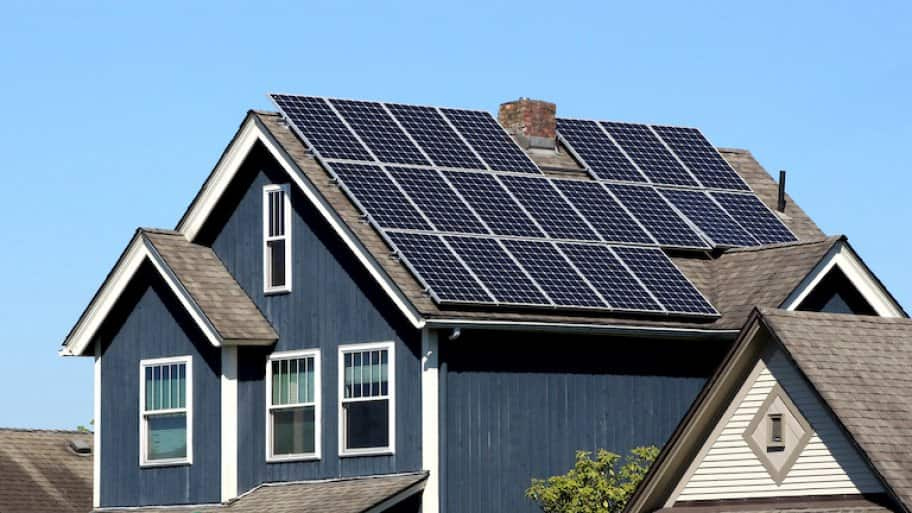 a blue house with roof covered in solar panels (Photo by © CLShebley - stock.adobe.com)