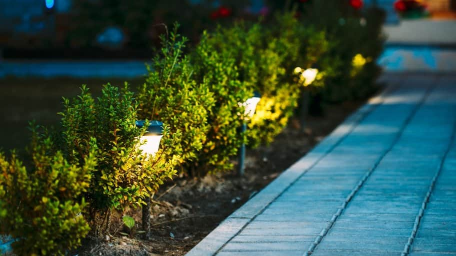 solar-powered torches along walkway in front of home at night