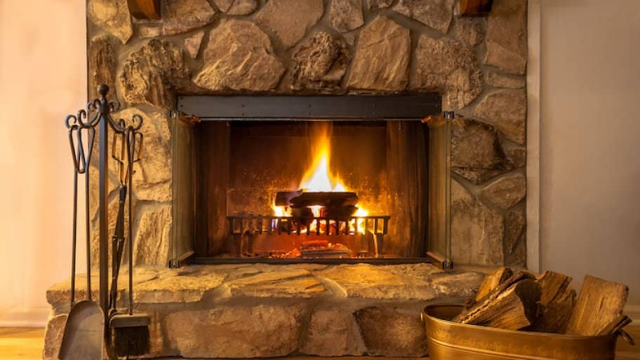 a stone fireplace with wood and fire with a bucket of firewood to the right
