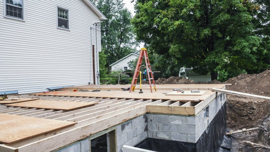 The subfloor covering a new home addition basement foundation is in process of being built at a suburban residential in-law apartment construction building site. Various tools, construction material and a ladder are strewn about.